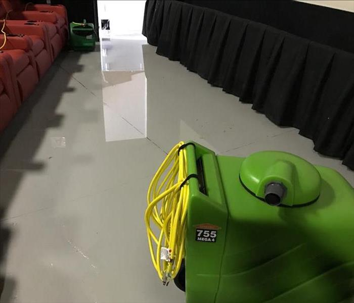 Kailua Cinemas theater floor flooding with green SERVPRO fans placed on floor
