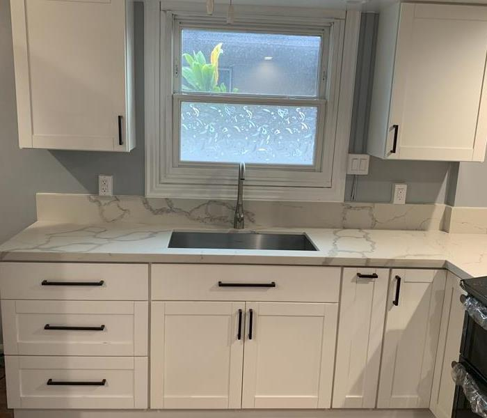 fresh white paint, new cabinets, and white marble counter tops in kitchen with large white trim around clear window