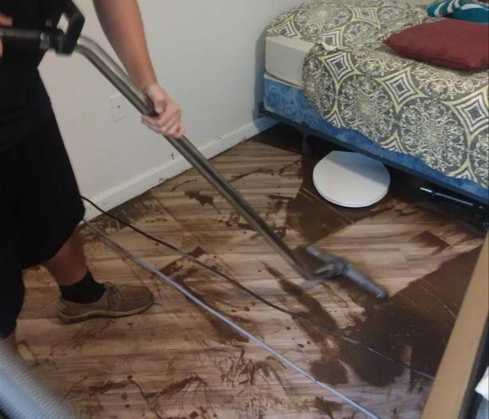 less brown water and dirt below bed, SERVPRO worker using water extractor
